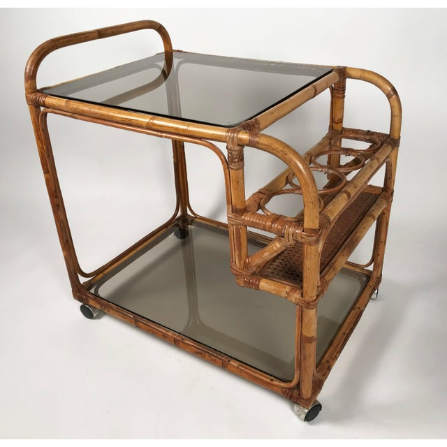 Rattan two tier bar cart featuring removable smoked glass shelves, caned bottle rack, rattan handle, and working castors....