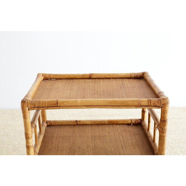 Diminutive bamboo and raffia rolling three-tier serving cart featuring a rattan and bamboo frame with open fretwork sides....