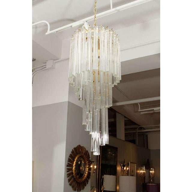 A very glamorous five-tier Murano glass foyer chandelier on brass frame.