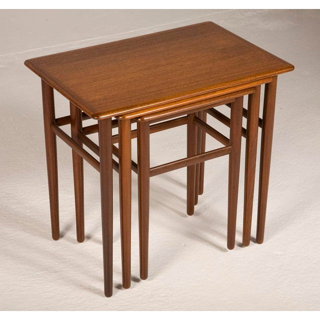 A beautiful set of three nesting tables in teak, each with bull-nose edges and round tapering legs, two with three...