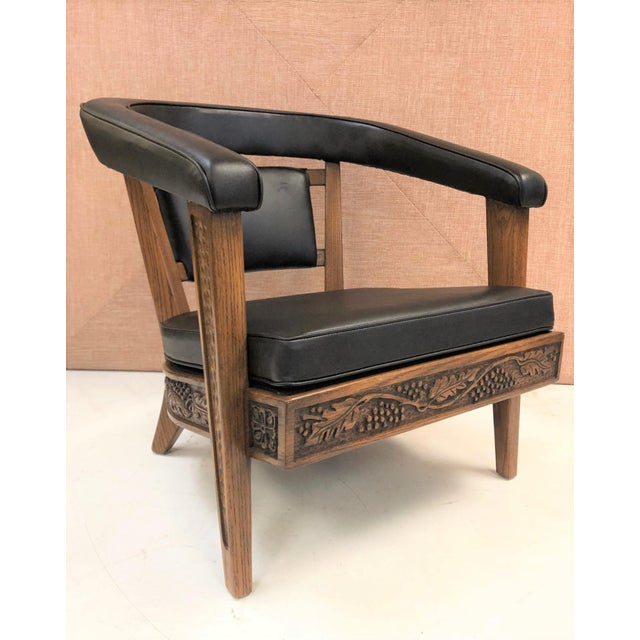 Pair of Romweber carved oak lounge chairs newly upholstered in black vinyl. Frame is heavily carved.