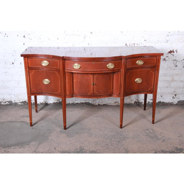 A gorgeous Hepplewhite style mahogany sideboard buffet by Baker Furniture. The sideboard features stunning mahogany wood...