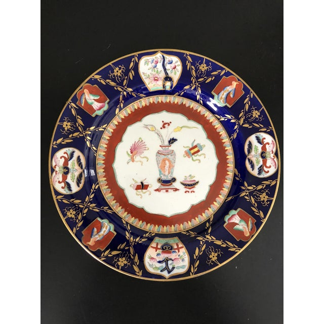 Pair of Ashworth Mason's ironstone plates in an Imari pattern. One on a cobalt blue background, one green. Mark on back....