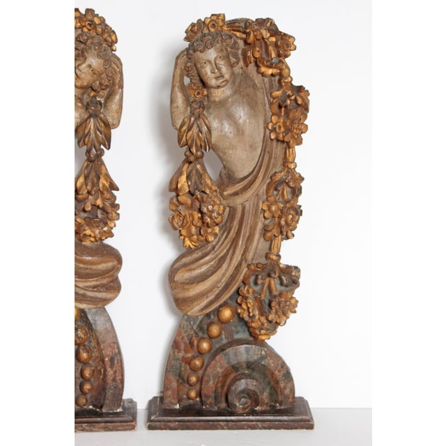 a pair of large free standing Italian carved and polychromed figures / male torsos / upper bodies draped in garlands of...