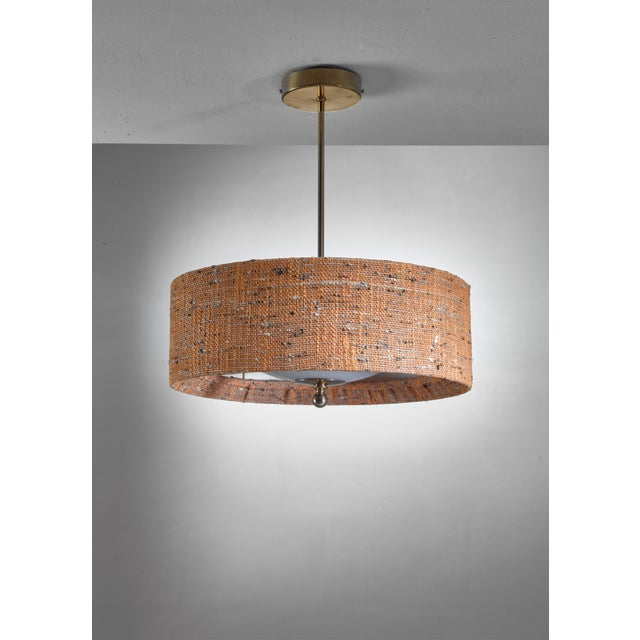 A mid-century pendant lamp from Sweden. The lamp has an orange/brown canvas shade with an opaline glass diffuser inside,...