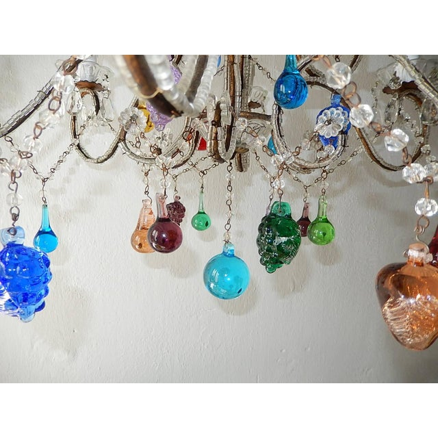 Housing six lights, sitting in crystal bobeches dripping with vintage crystal prisms. Beaded, florets and swags...