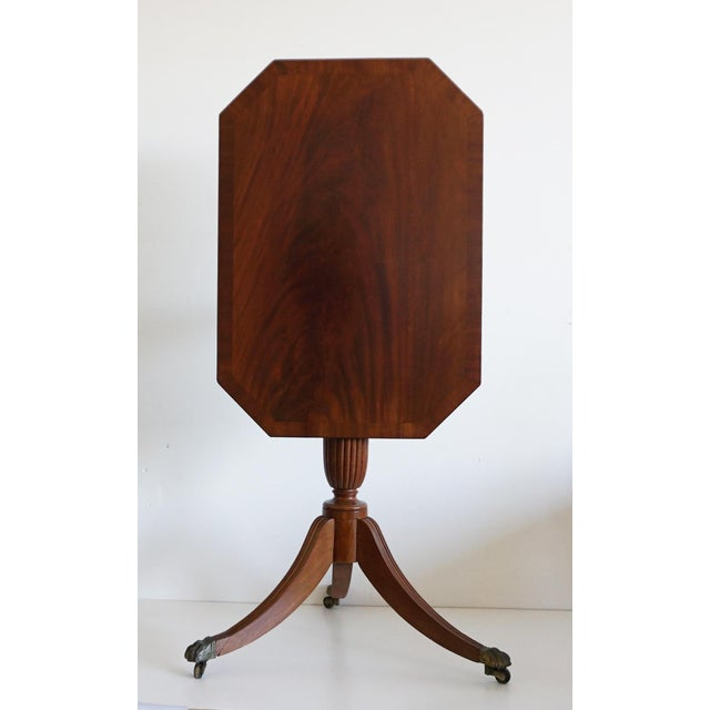 A mahogany tripod table . The top is of one piece solid mahogany with a tilt-top action secured with a brass latch. It...