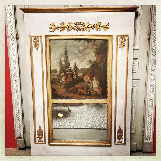 A French Louis XVI style trumeau mirror with a painted and parcel gilded finish with an oil painting depicting Chevalier.