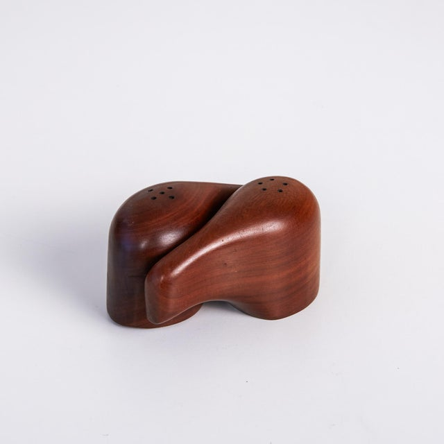 Set of Don Shoemaker for Señal salt and pepper shakers. The hand carved minimalist mahogany shakers feature a interlocking...