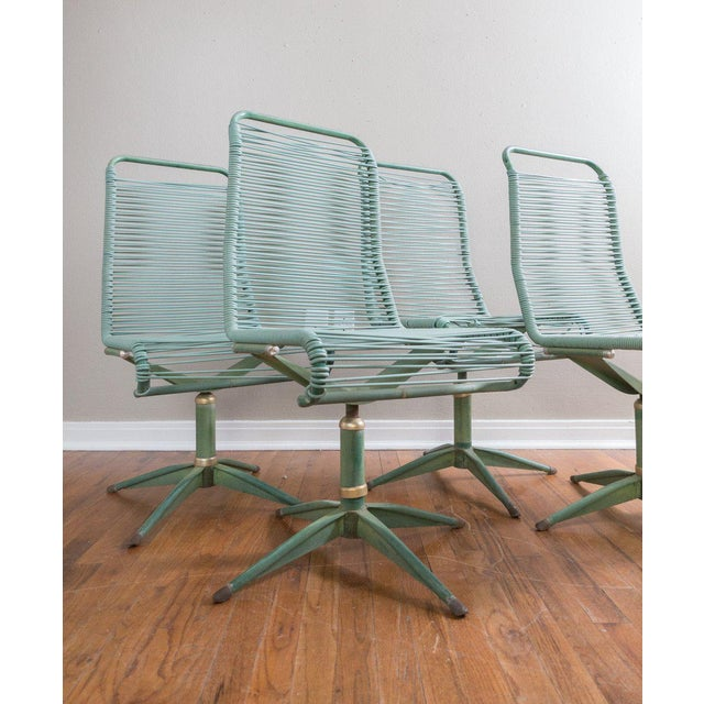 This is a set of 4 Ames Aire Cabana Star line mid century patio dining chairs. They are a teal green color on the metal...