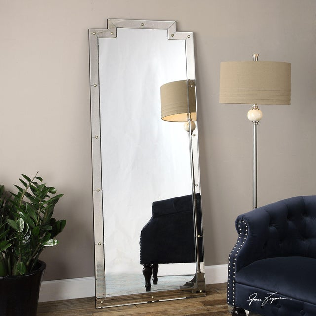A studded floor mirror whose frame is constructed of smoked, beveled mirrors accented with rounded, antiqued gold nail heads.