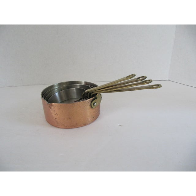 "Set of 4 vintage lacquered copper and brass measuring cups. Marked ""Korea."" Some wear, scratches, tarnish and spots."