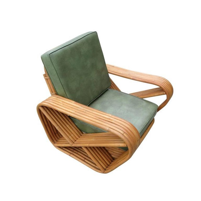 Designed in the manner of Paul Frankl, this six-strand, rattan lounge chair features square pretzel arms and a Classic...
