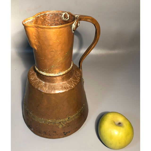 ITEM DESCRIPTION: An impressive, hand hammered, primitive 1800s copper pitcher. Solid copper with brass welding. Riveted...