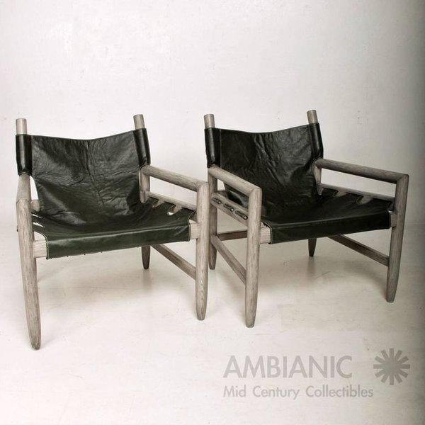 For your consideration a pair of Safari lounge chairs. Cerused wood in grey finish with green leather seat slings....
