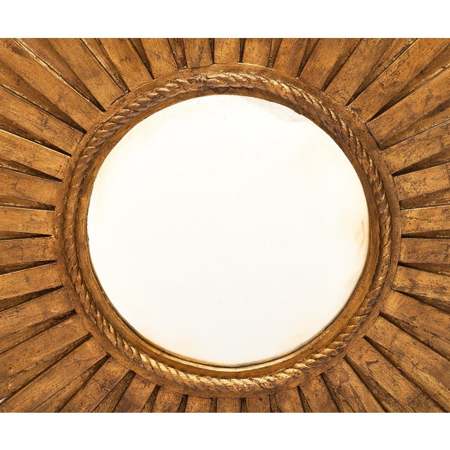 A vintage pair of large sunburst mirrors featuring three layers of hand-carved and gold-leafed wooden rays. The round...