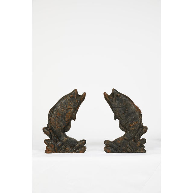 Pair of early 20th century American leaping game fish andirons well modeled in cast iron of opposing figures and having an...