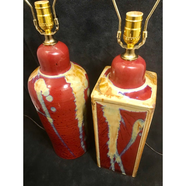 A pair - one round and one square Jim Lauer signed studio pottery art lamps. Great quality lamps featuring an oxblood-...