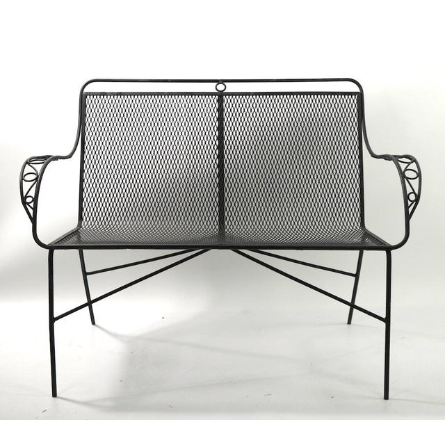 Chic and stylish wrought iron and metal mesh settee attributed to Woodard, in original black paint finish.Priced and...