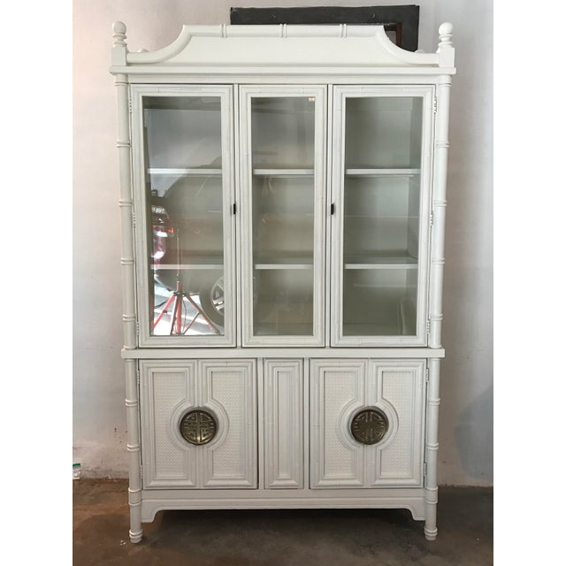 A vintage chinoiserie style faux bamboo china cabinet newly painted inside and out in an antique white milk paint. Top two...