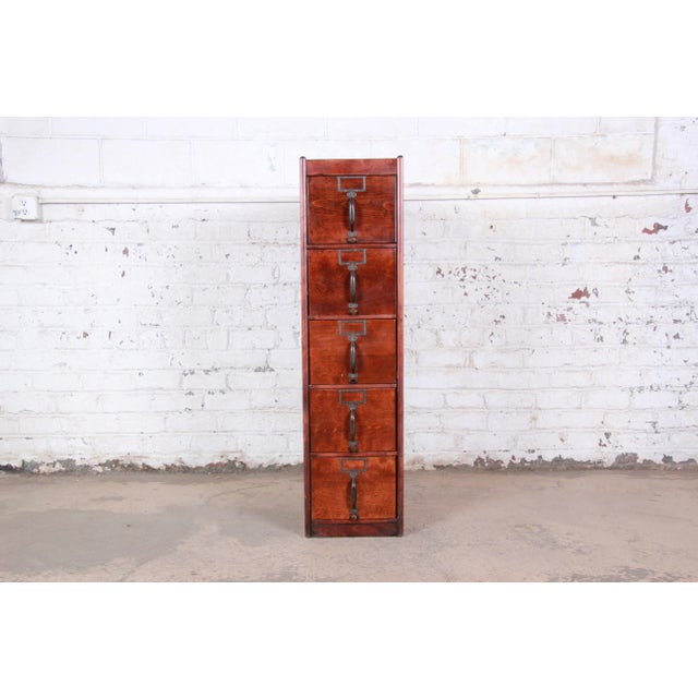 A very nice antique 5-drawer wood filing cabinet. The cabinet features gorgeous wood grain and original hardware. It...