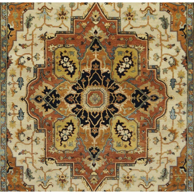 This beautiful rug is hand made, made in India. It features a pattern in a vibrant combination of ivory, rust, and blue,...