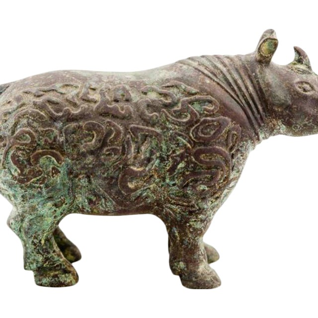Verdigris bronze double-horned rhinoceros with archaic Chinese motif. Designed by Lucia Lawrence with inspiration from...