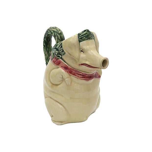 Antique satyrical majolica pig jug. He is wearing a laurel crown on his head and has a ham hanging from a red satin sash....