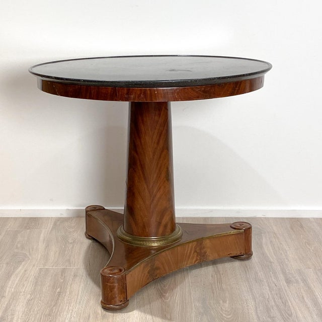A French Empire Style mahogany center table with a gray marble top and gilt bronze mounts.