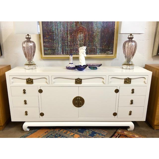Vintage painted credenza in soft white. Brass hardware is original. This is a very well kept piece of furniture.