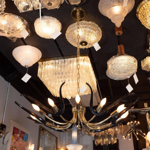 This rare and graphic Mid-Century Modern chandelier was realized in the United States, circa 1960. It features an...