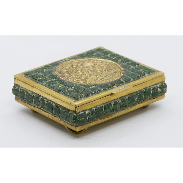 Stunning brass and glass mosaic box by Mexican artist. The box four raised brass feet. On the top is the Mayan medallion...