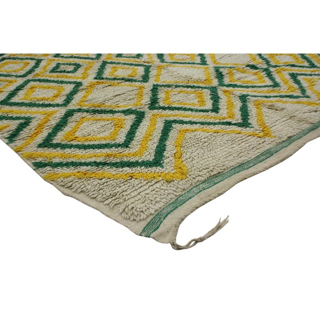 Say goodbye to winter blues and dial up the cheer with this green and yellow vintage Berber Moroccan rug. This impeccably...