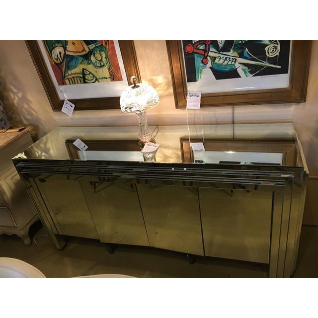 A large four-door mirrored side board or dresser, beveled top with stepup sides and front. Interior of cabinet sides is 29...