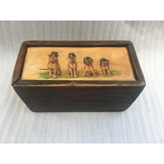 A fantastic old wooden money box with a slide mystery lid. Dovetail construction features a whimsical foursome of smoking...
