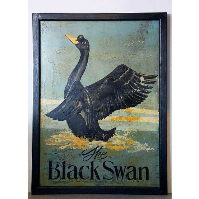 An authentic English pub sign (one-sided) featuring a painting of a black swan upon the water, entitled: The Black Swan. A...