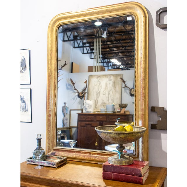 This is an antique Louis Philippe Mirror, discovered in France. The design on the giltwood frame is a floral pattern with...