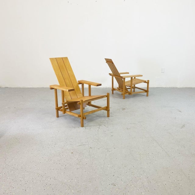 A beautiful iteration of the red and blue chair originally designed by Gerrit Rietveld. This pair realized in natural...