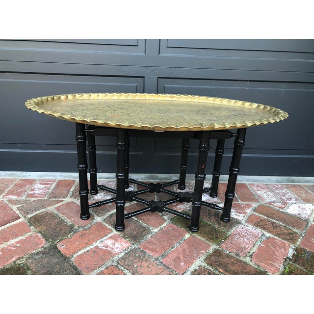 Traditional Turkish brass tray sits atop eight legged black wood base. Faux bamboo table legs are connected by a lattice...