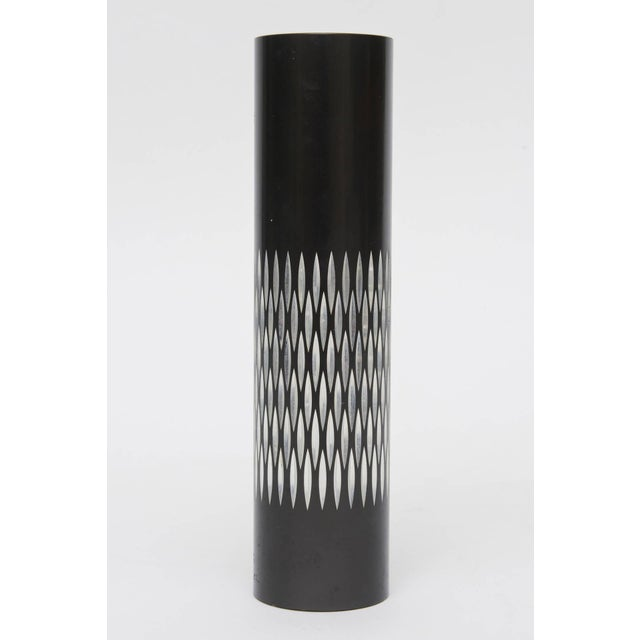 This wonderful English graphic cylinder and period black metal vase with textured diamond patterned indented silver is...