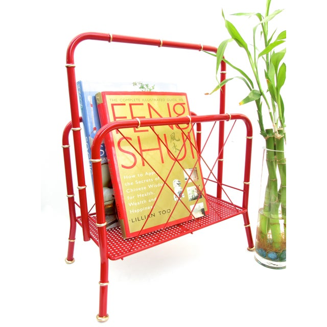 Chic and unique, this vintage magazine rack boasts a Chinoiserie-inspired faux bamboo red metal frame, glam gold gilt...