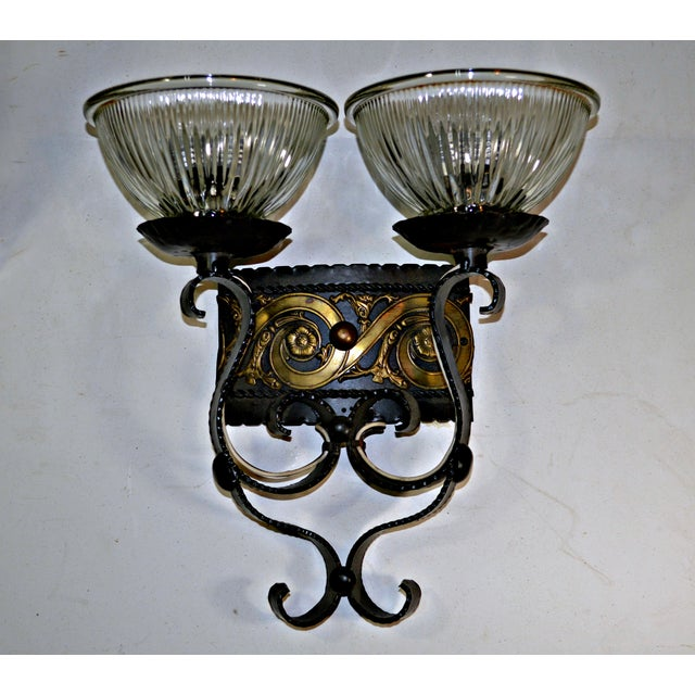 Offered is an elegant two light single sconce. This piece features black and gold enameled metal, with cup shaped fluted...