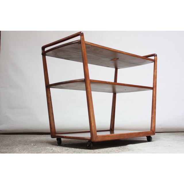 1950s three-tier sculpted walnut bar cart / serving trolley on caster wheels with a black laminated top shelf manufactured...