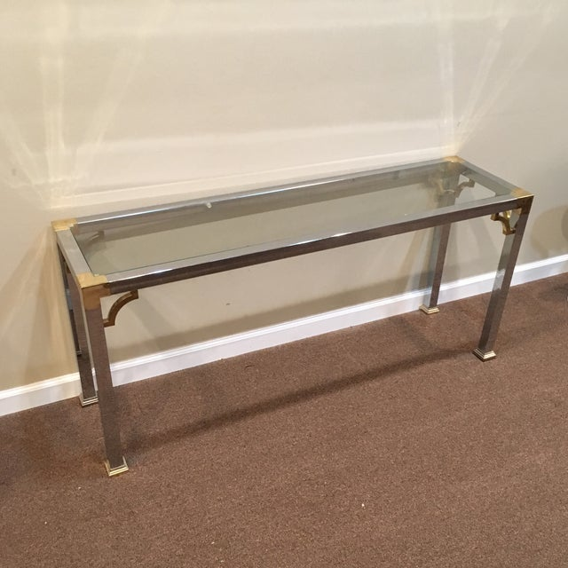 Posh console table in a neo-Chippendale style by mastercraft. Chrome finish with brass accents and recessed glass top.