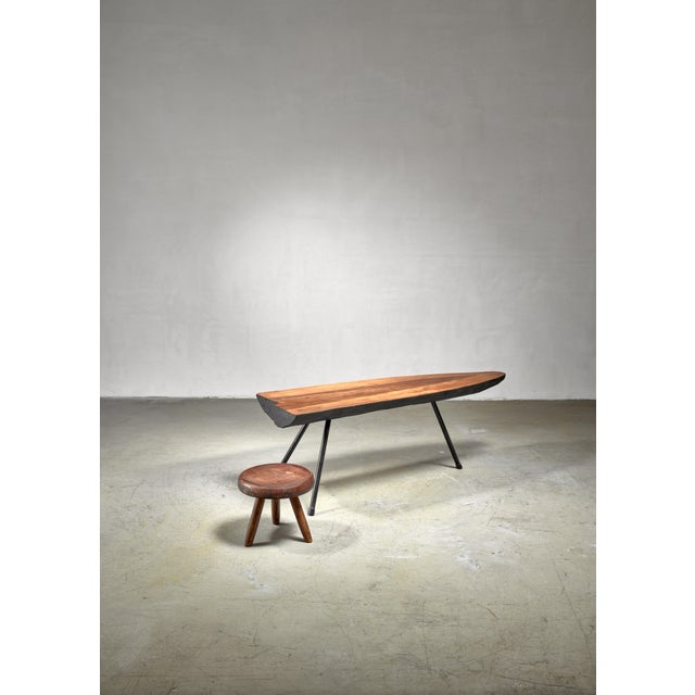 A tree trunk table by Austrian designer Carl Auböck, from circa 1950. The table has three black lacquered metal legs and a...