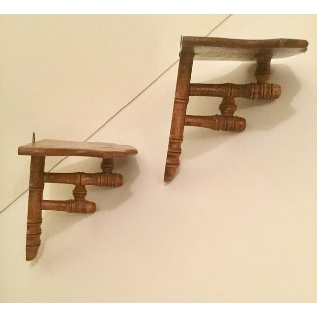 Early hand crafted solid wood wall shelves with scalloped tops. Mounting hardware includes top & bottom screw holes to...