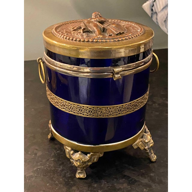 Antique royal blue glass trinket box with gold mounts and feet with faces. Also has a figural top. 19th Century from...