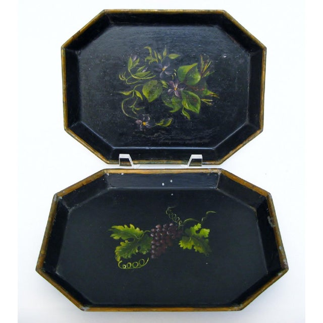 Hand-painted early 20th century tole trays in black with violet-shaded themes, one with a flower motif, one with a grape...