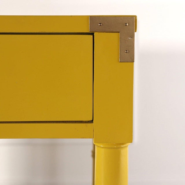 Bright and shiny lacquered yellow campaign desk by Dixie with a shiny gold finish to brass hardware. Faux bamboo leg. Nice...