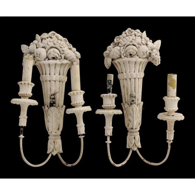 Painted white wooden sconces with cornucopia and basket detail and two ams. They need restoration. Priced as is for the pair.
